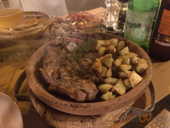 Bistecca Scottona con Patate cotta su testo in forno a legna con legno di faggio
