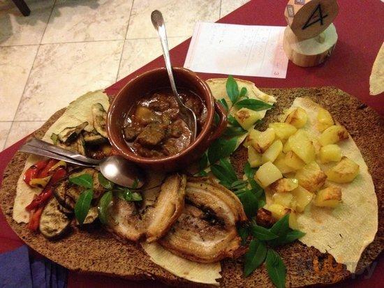 Maialino arrotolato al forno e asino in umido con patate al forno e verdure grigliate